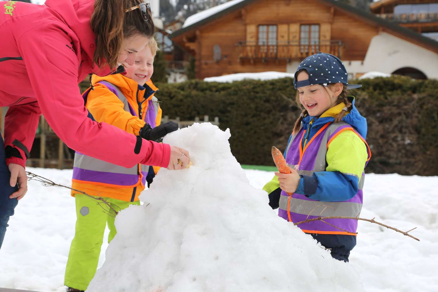 children playing in the snow building a snowman